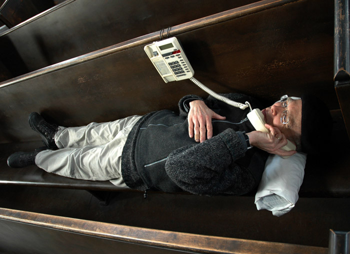 John Shipman, in a coffin pew listening to a coffin phone, 2010